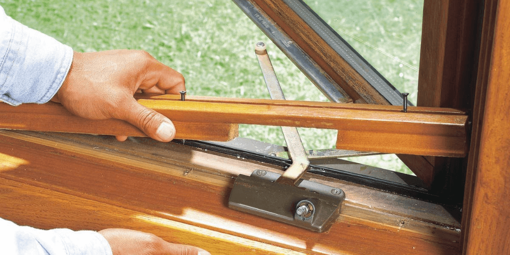 hardware on a window that is bent and broken. this is a sign its time to replace the windows