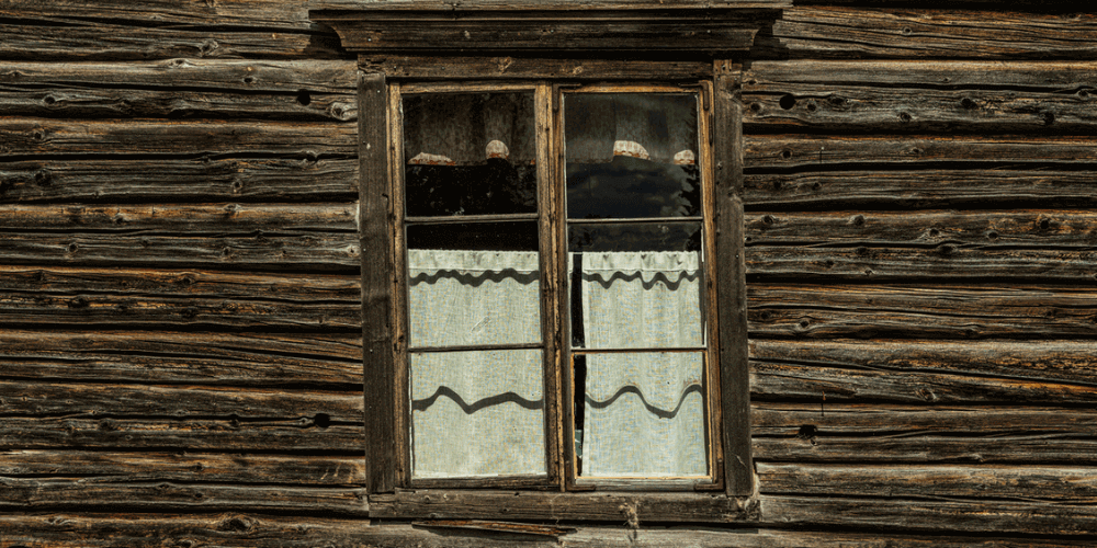 Warped windows are a sign that its time to replace them. Old window on a dark wooden house that is warped and leaning left