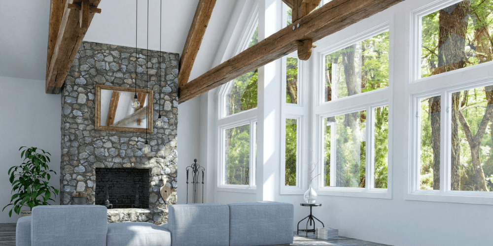 a bright home with a stone fireplace and exposed wooden beams in the living room with big windows across the whole right wall